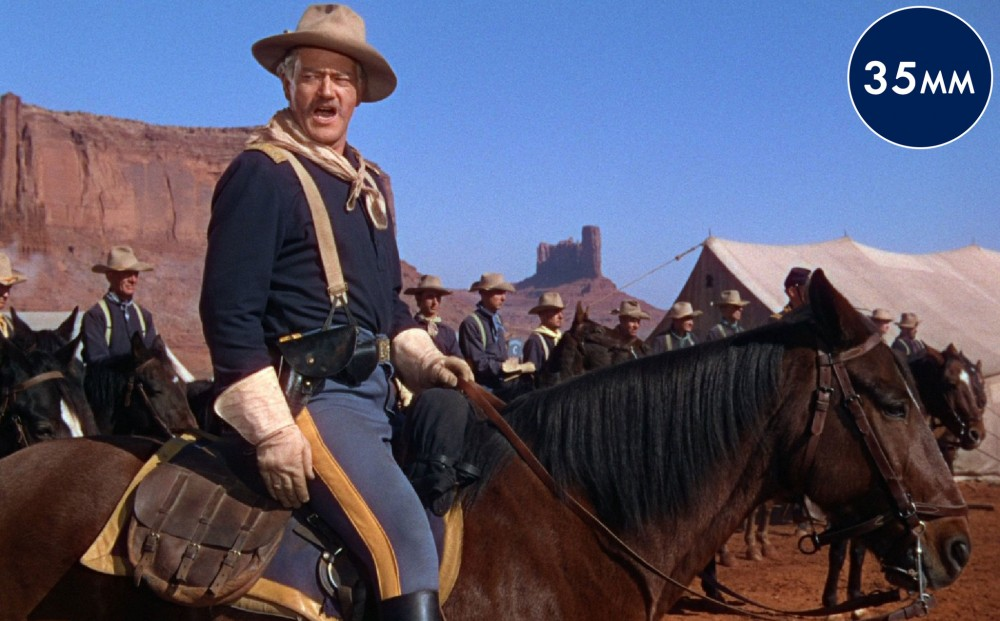 A group of men on horses in an army encampment; actor John Wayne is in the foreground shouting.