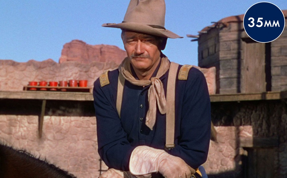 Actor John Wayne sits on a horse, looking skeptical.
