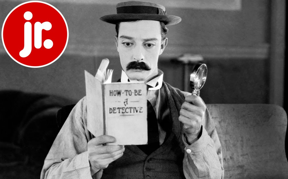 Buster Keaton holds up a magnifying glass and a book with the title