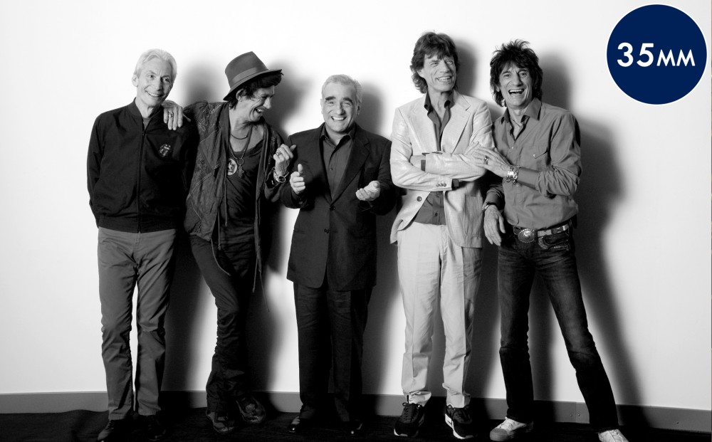 Black and white image of the four main members of The Rolling Stones, standing by a wall with Martin Scorsese.