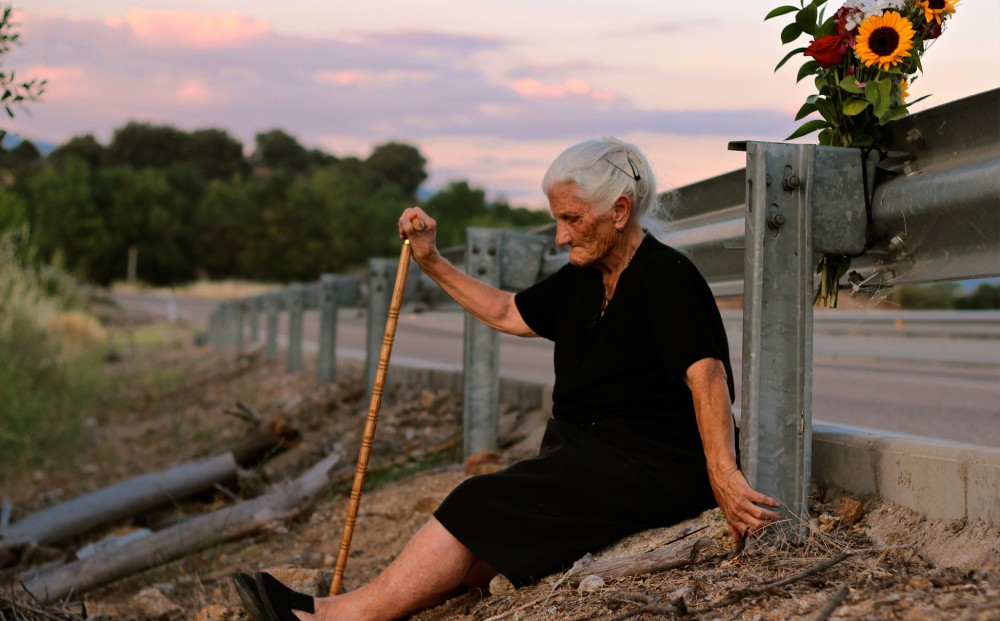 In a film still from THE SILENCE OF OTHERS: An elderly woman sits in the dirt, by the railing on the side of a road; she holds a cane in her right hand.