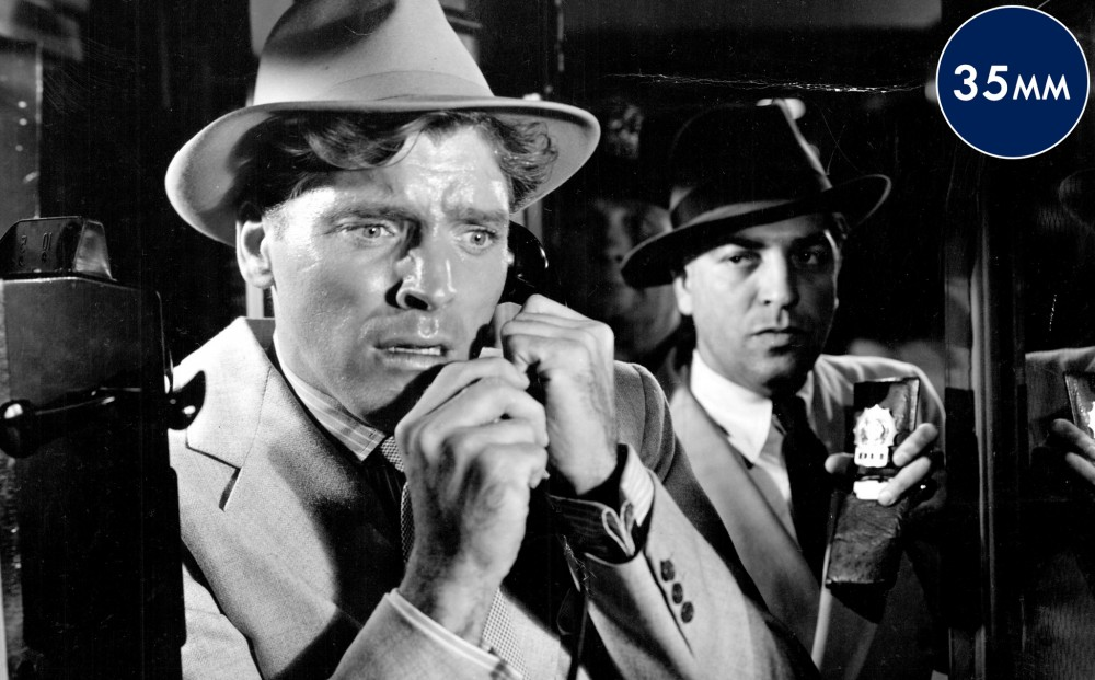 Actor Burt Lancaster, in the foreground, grips a payphone and looks worried; an officer in the background. presents his badge.