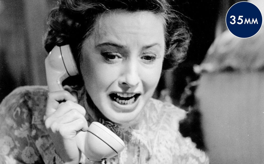 Actor Barbara Stanwyck speaks into a phone, looking extremely upset.