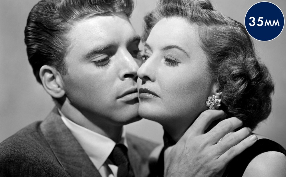 Actor Burt Lancaster has his hand on Barbara Stanwyck's neck; their faces are close together but they don't look at each other.