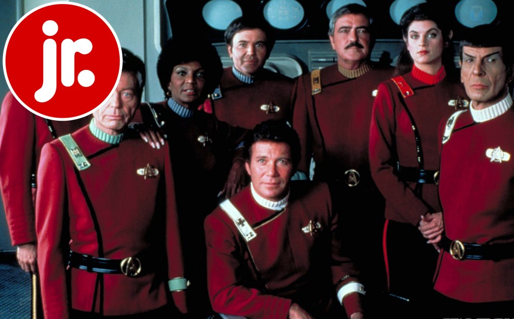 Eight members of the spaceship crew pose in their red uniforms.