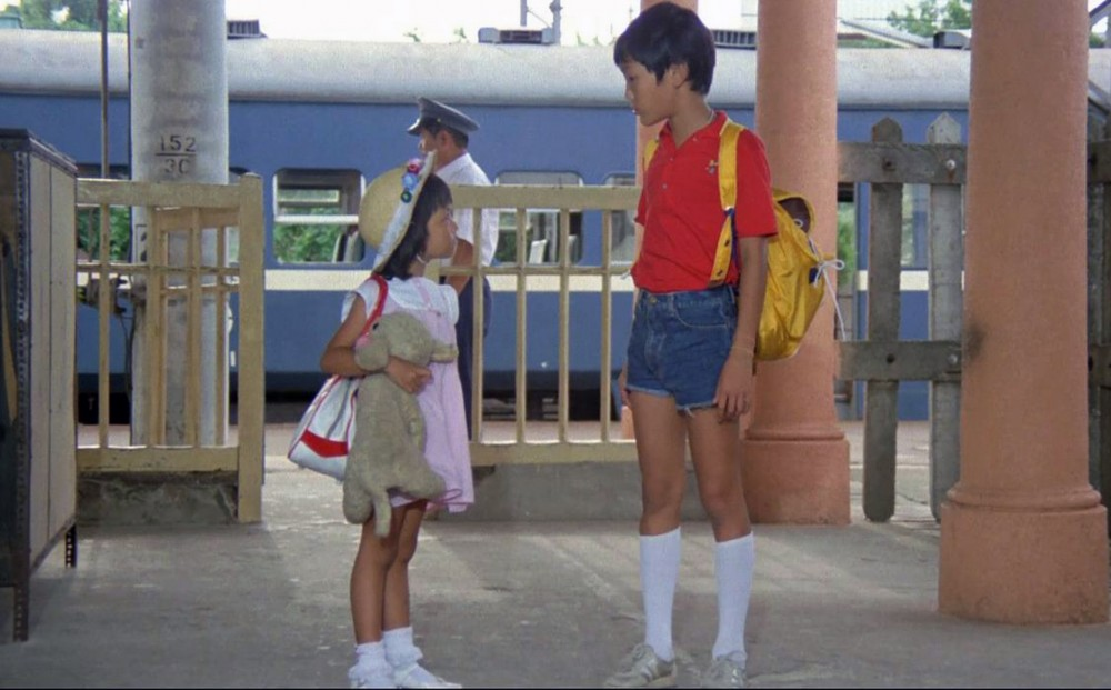 A very young girl holding a stuffed animal and a young boy stand together at a train station.