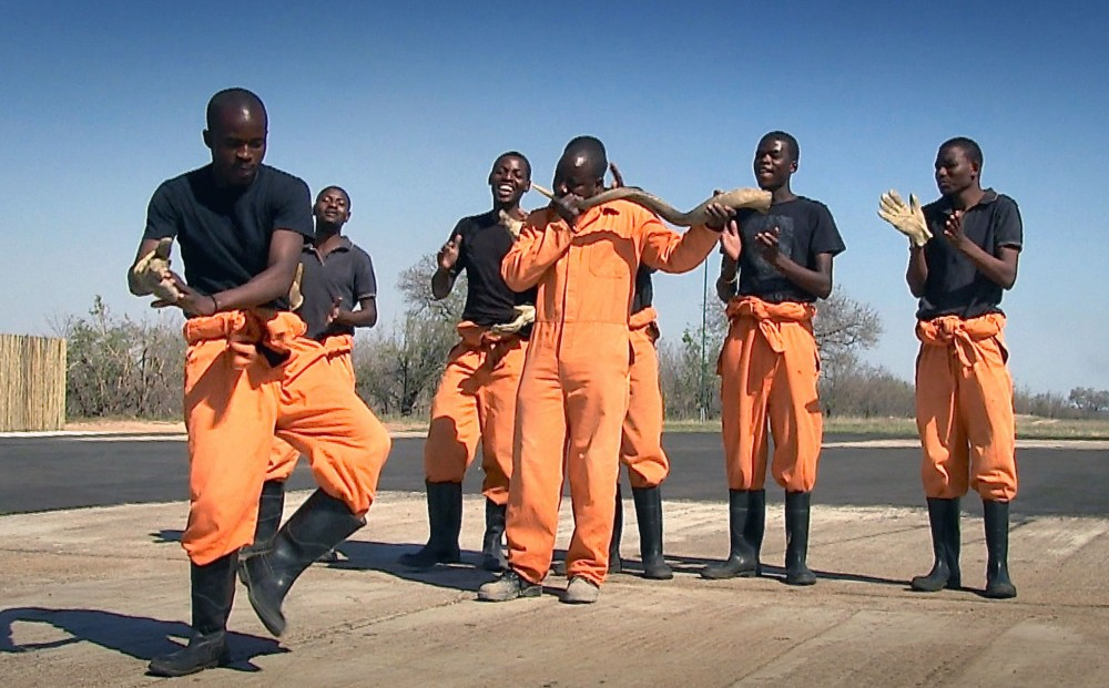From TAP WORLD - Six men wearing orange jumpsuits or pants standing in a group. One dances, another blows into an instrument, and the rest clap their hands.