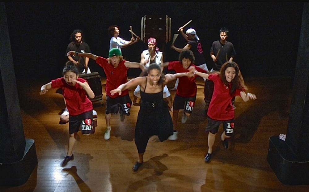 From TAP WORLD - Five tap dancers perform on a stage, with five musicians playing taiko and other drums in the back.