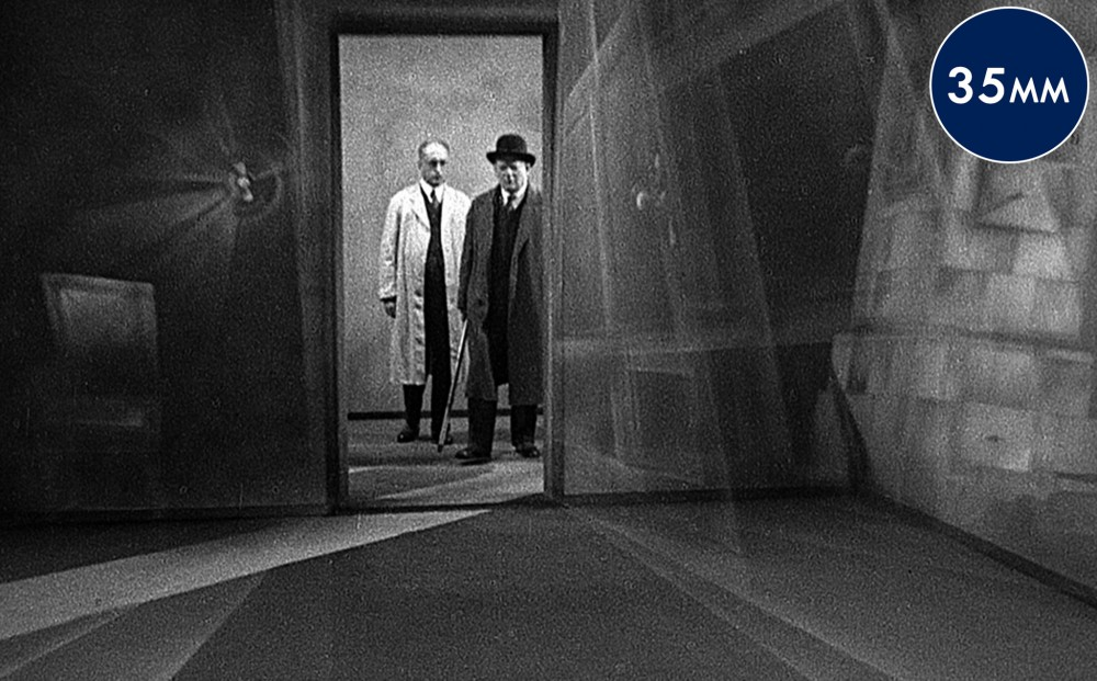 Two men stand in a doorway, one in a white coat and one in a black coat and bowler hat.