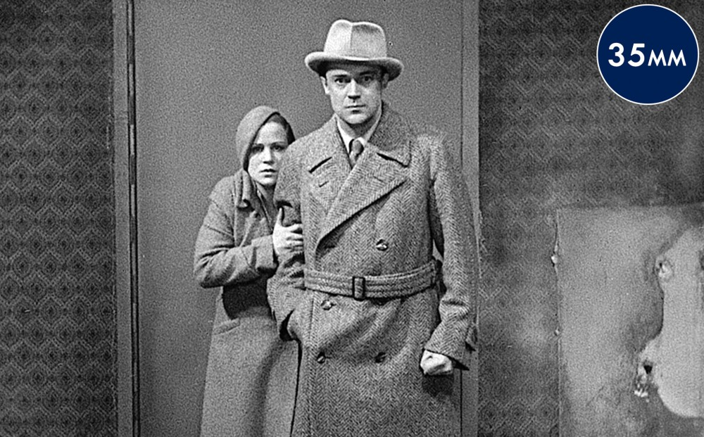 A man and woman stand in front of a door. He has one hand in his pocket and the other is clenched into a fist; she clutches his arm, stands slightly behind him, and looks frightened.