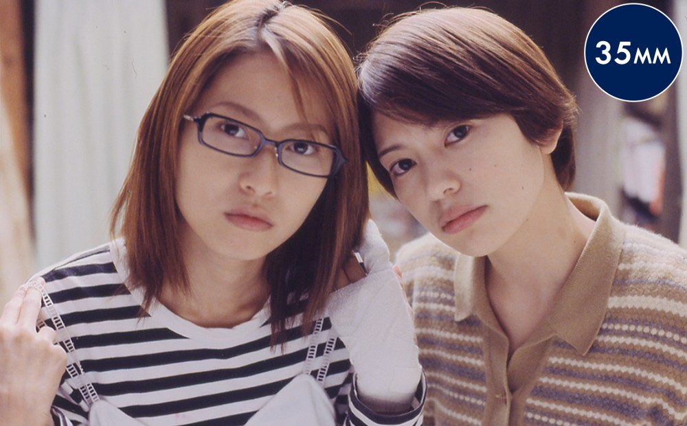 Two women look intently at something off-camera, their heads close together. One's hand is wrapped in a white bandage.