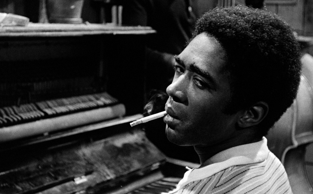 A man sits at a piano with a cigarette in his mouth.