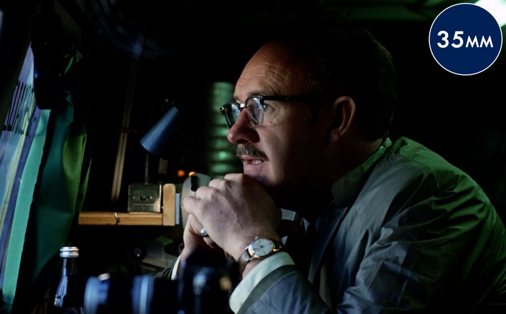 Actor Gene Hackman sits with his head rested on his hands, observing something through a window.