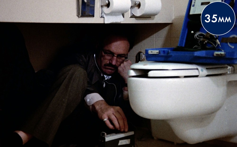 Actor Gene Hackman crouches by a toilet, using equipment to listen intently to something through headphones.