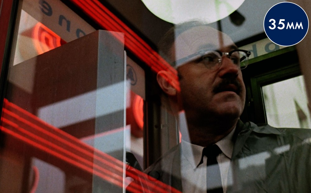 Actor Gene Hackman, seen through a window on which neon lights are reflected.
