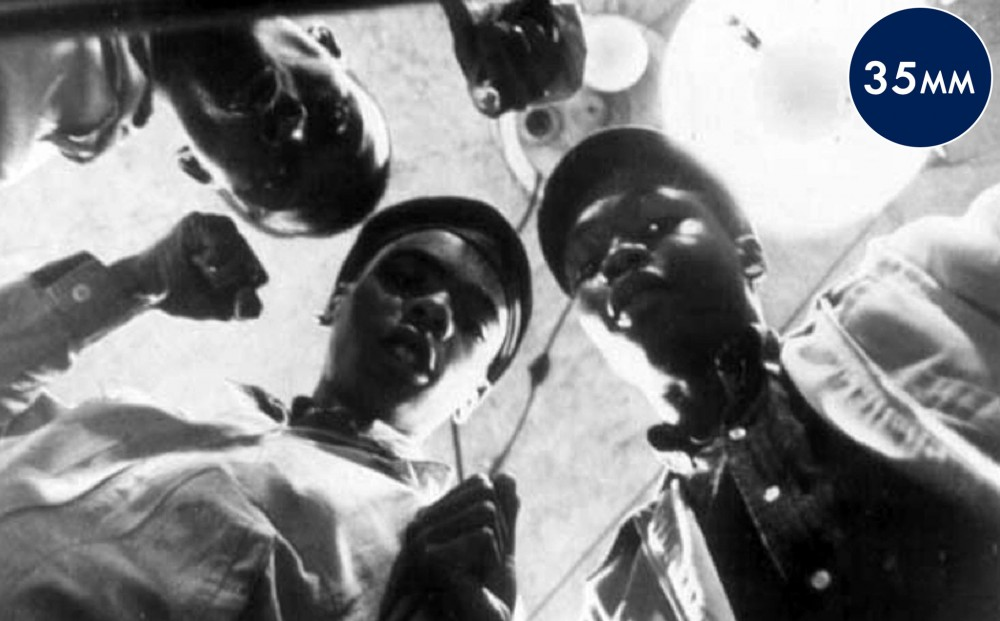 Three young men viewed from below; they look down into the camera.