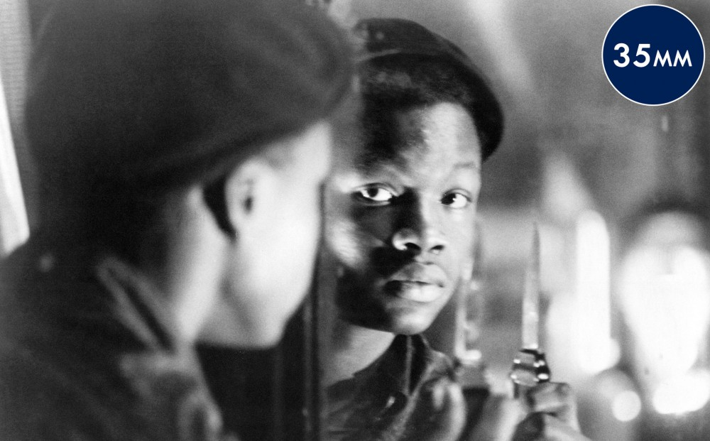 A young man holds up a knife and looks at his reflection.