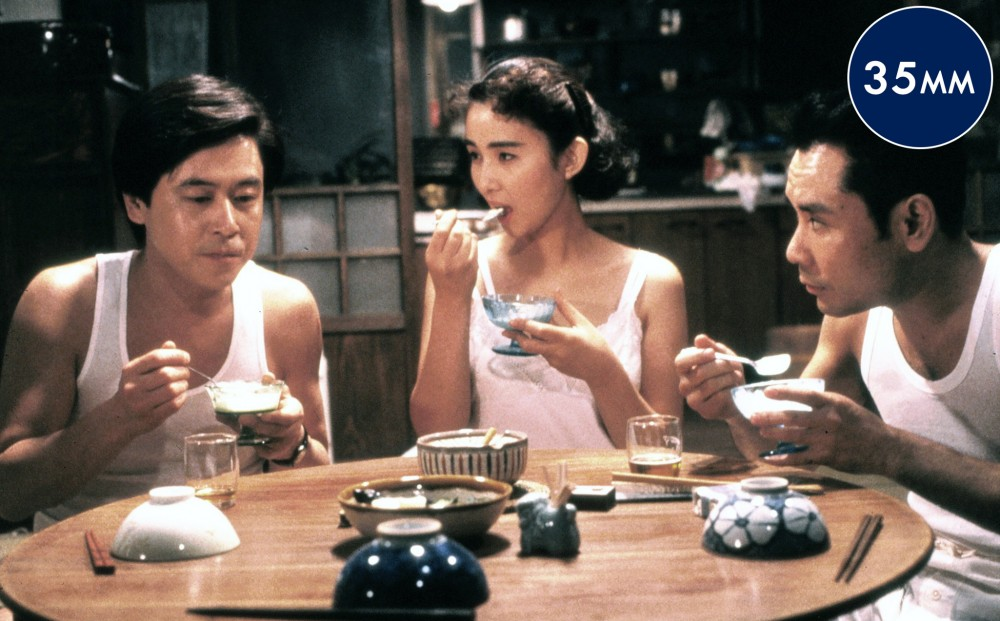 Two men and a woman in white tank tops sit around a table and eat.