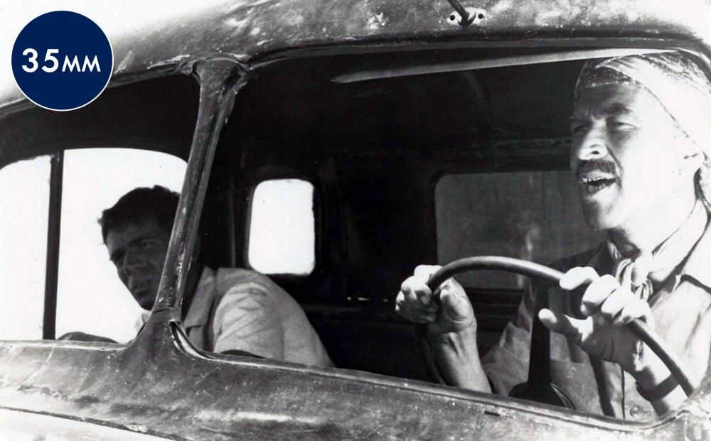 Two men sit in the front seat of a truck, one driving.