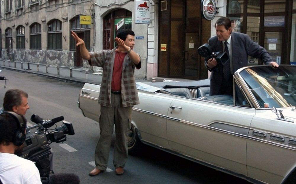 A man stands in a convertible holding a camera, a man outside of the car on the street motions towards the sidewalk, where a camera crew is crouched.