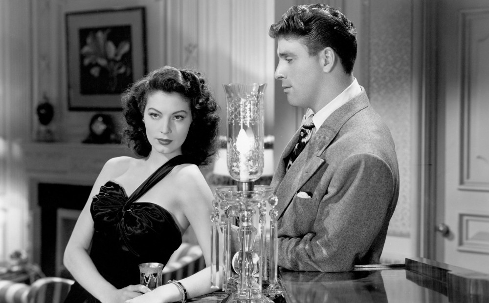 Actor Ava Gardner looks off into the distance in a living room; Burt Lancaster looks at her.