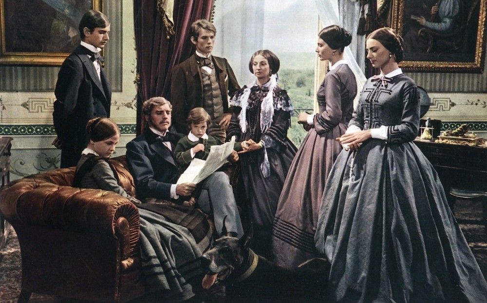 Actor Burt Lancaster sits on a sofa in a living room, surrounded by seven family members.