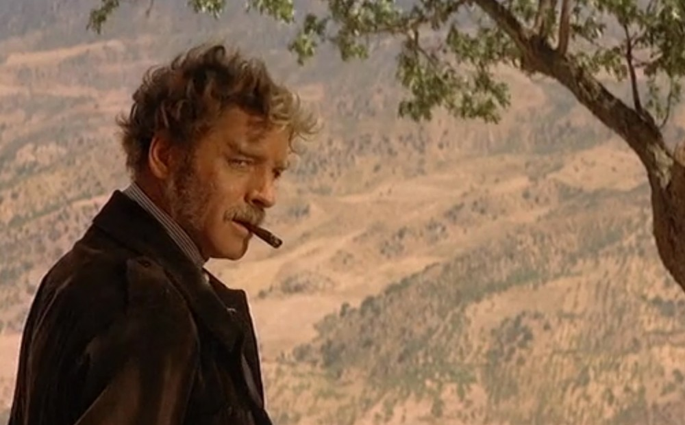 Actor Burt Lancaster stands in profile, smoking, with the hills of Sicily in the background.