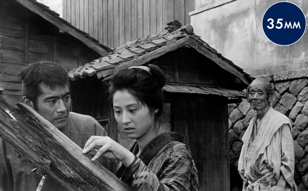 A woman touches and looks at a broken bit of a wooden structure, while a man looks at her intently, and an elderly man watches them both from a few feet away.