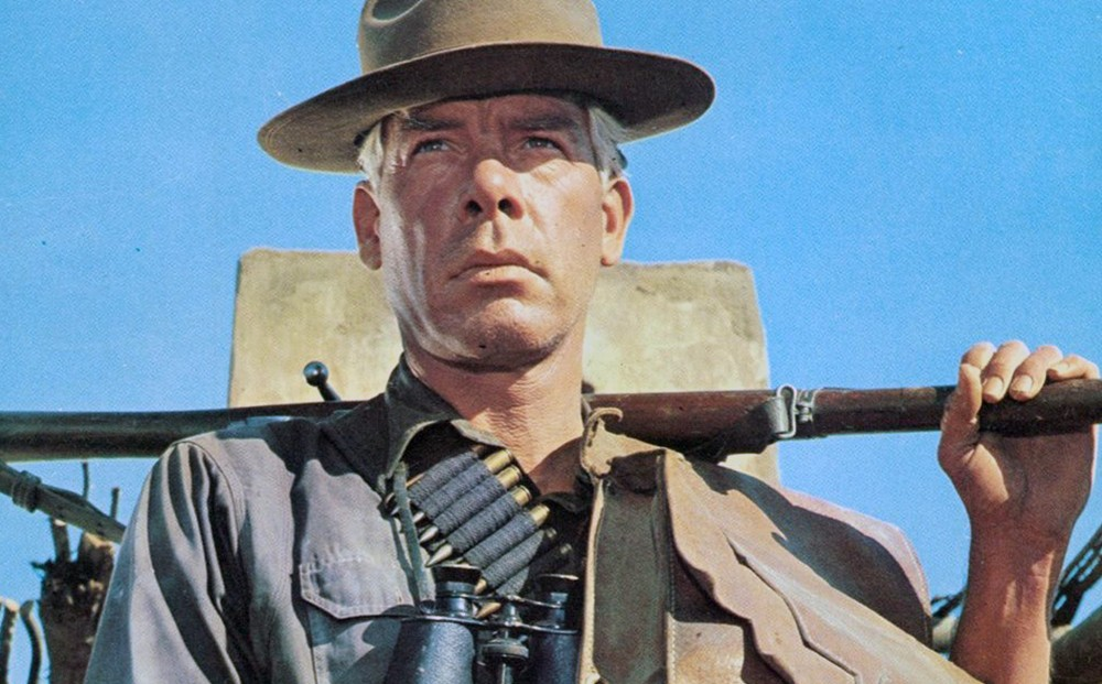Close-up on Actor Lee Marvin, wearing a hat, binoculars, and a bandolier, and holding a gun.