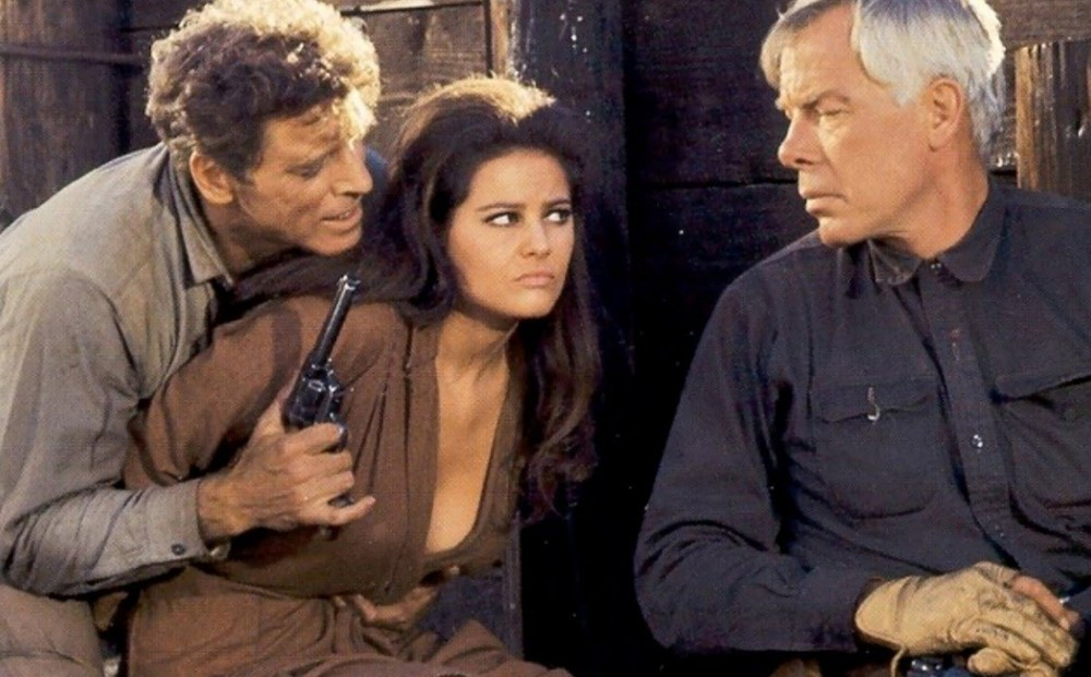Actor Burt Lancaster holds Claudia Cardinale's arms behind her back and holds a gun, while Lee Marvin looks on impassively.