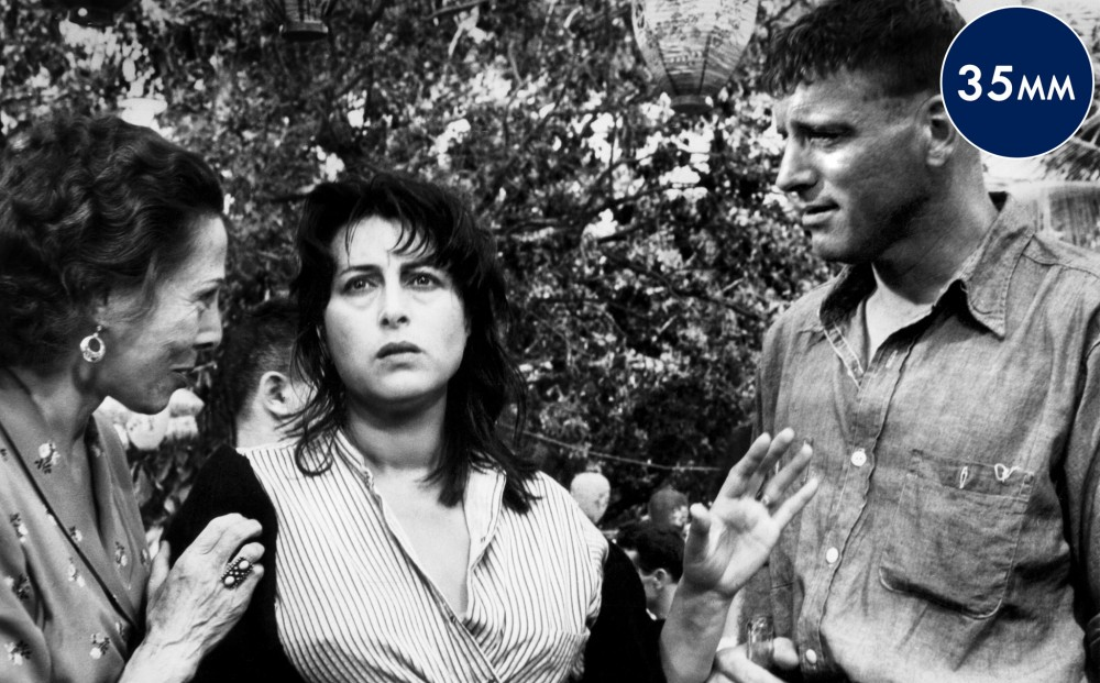 Actor Anna Magnani stands between Burt Lancaster and a woman who puts her hand on Magnani's shoulder.