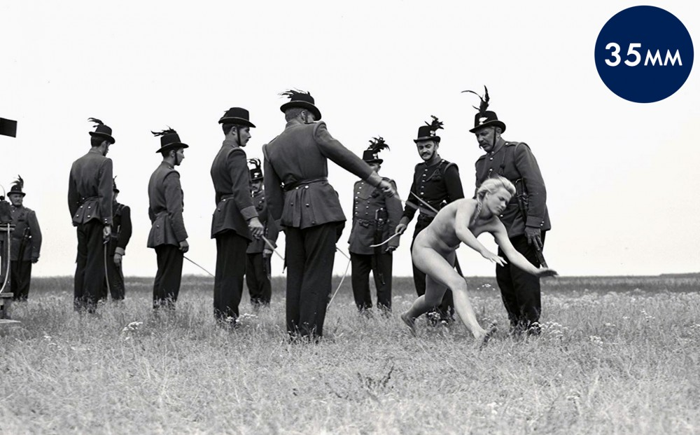 A naked woman falls to the ground between two rows of soldiers in a field.