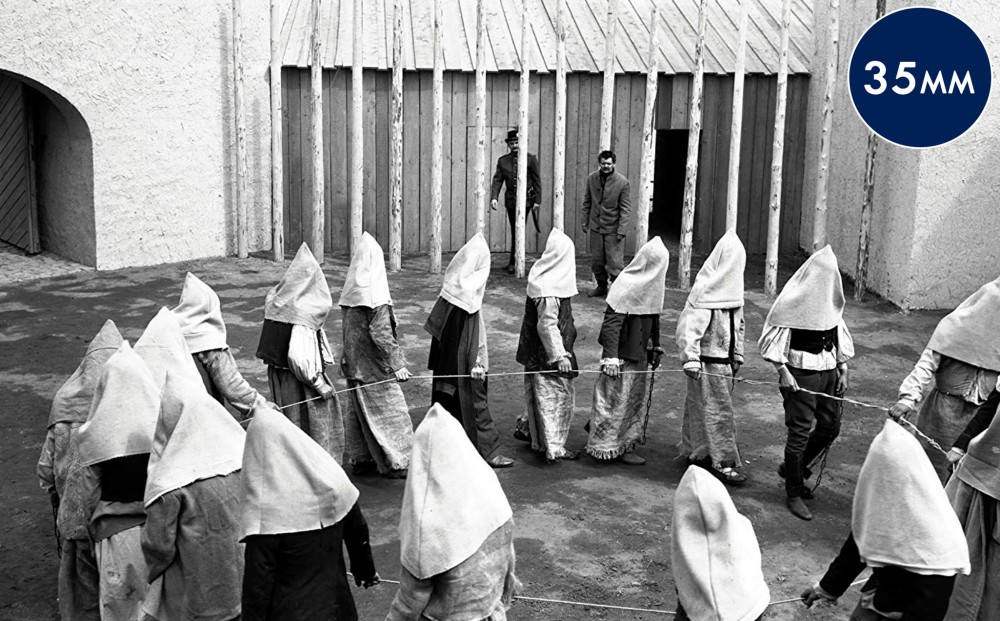 A group of prisoners with hoods over their heads all hold on to a rope and walk in a circle.