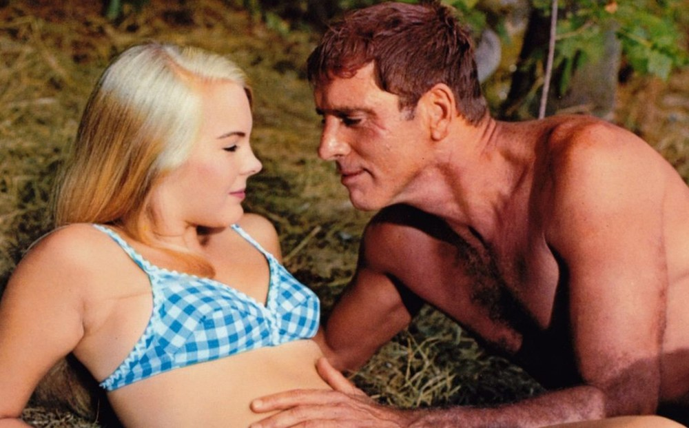 Actors Burt Lancaster and Janet Landgard wear swimsuits; he caresses her stomach.