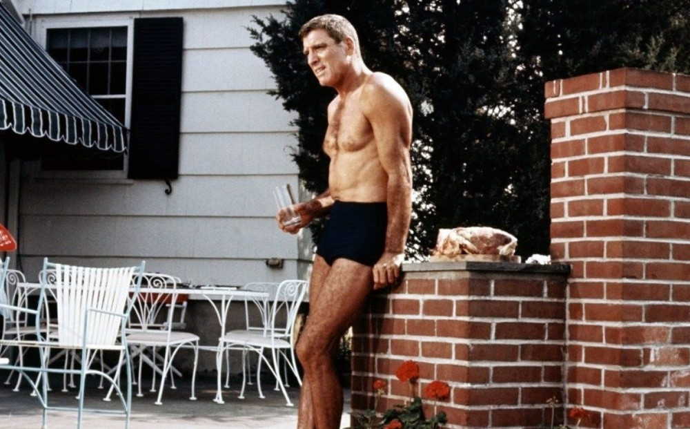 Actor Burt Lancaster, wearing swim trunks, leans on a wall by the side of a pool, holding a glass of water.