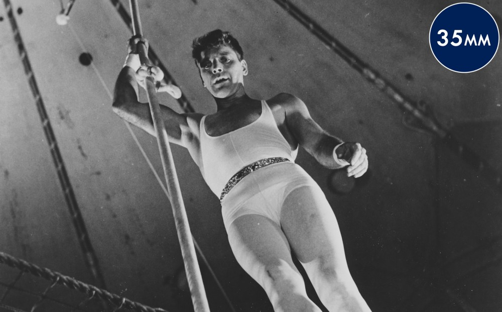 Actor Burt Lancaster stands far off the ground in a circus tent, wearing a trapeze artist costume.