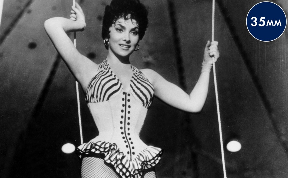 Actor Gina Lollobrigida holds onto ropes in a circus tent, wearing a trapeze artist costume.