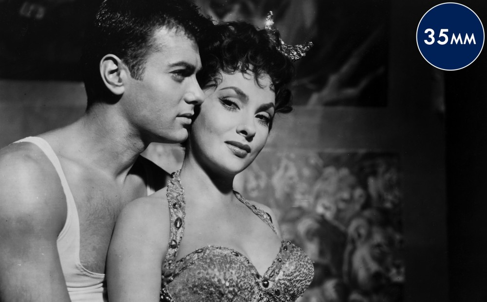 Actor Tony Curtis embraces Gina Lollobrigida, both wear trapeze artist costumes.