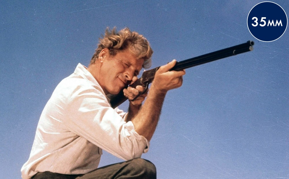 Actor Burt Lancaster aims a shotgun.