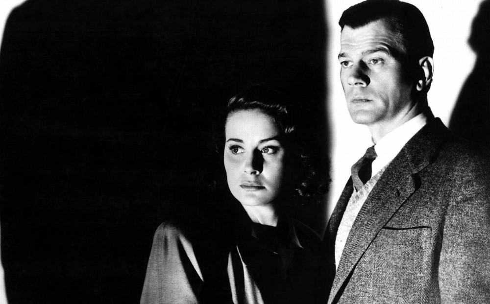 Actors Alida Valli and Joseph Cotten, standing in shadow.