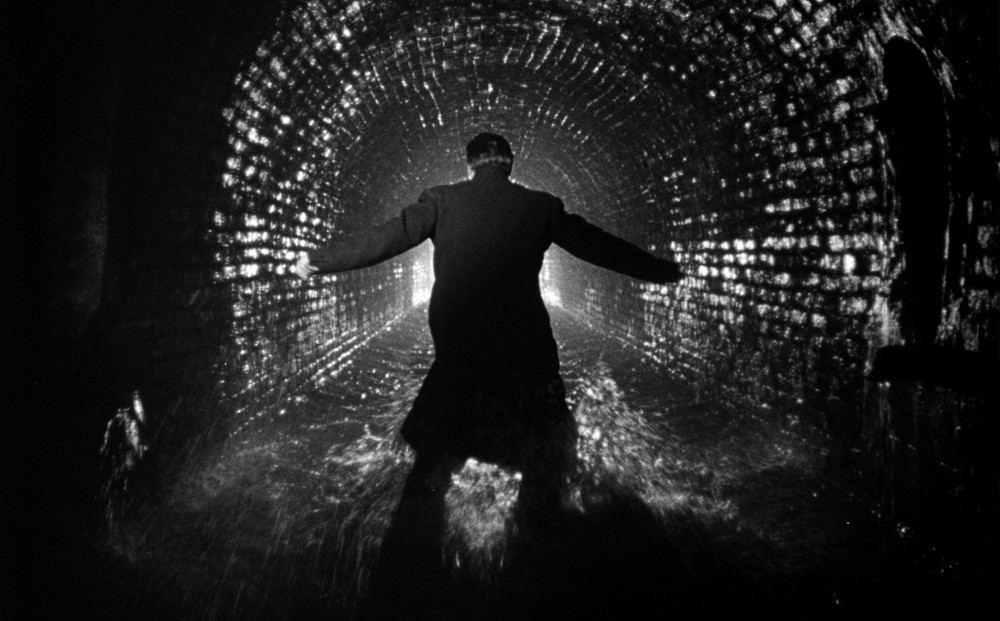 A man in a long coat stands in a tunnel, his back to the camera.