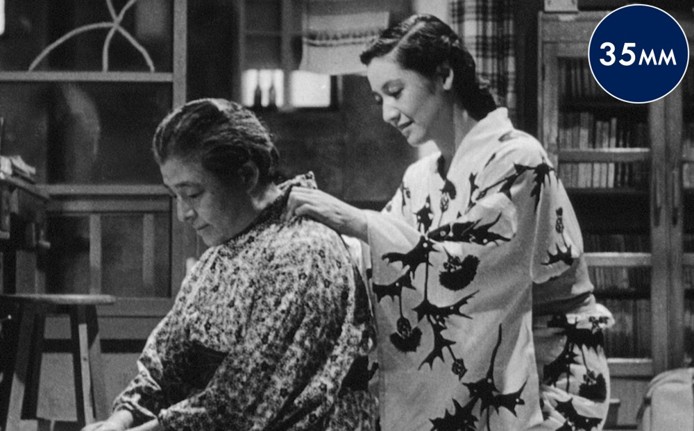 One woman helps another get dressed in her kimono.