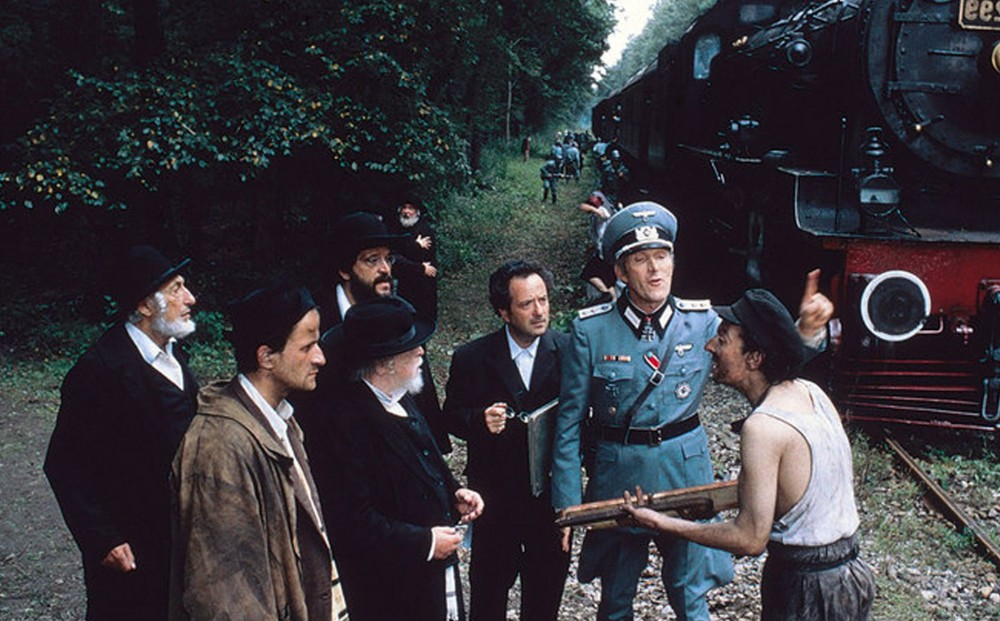A man in Nazi uniform stands by a train; a group of men stand around him, one holding a gun. More Nazis are in the background, alongside the train.