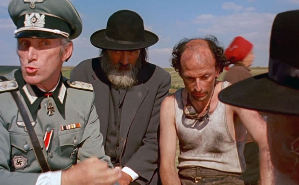 A man in Nazi uniform stands next to two ragged, dirty-looking men - one in black suit and black hat, the other in a dirty tank top with goggles around his neck.