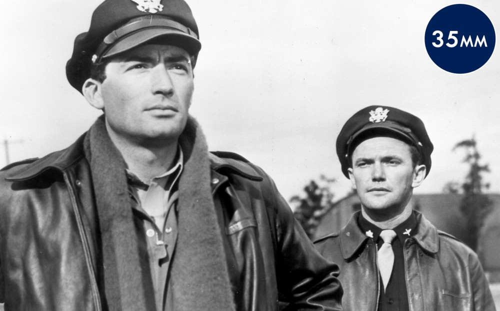 Gregory Peck and another actor in Air Force uniforms stand next to each other.