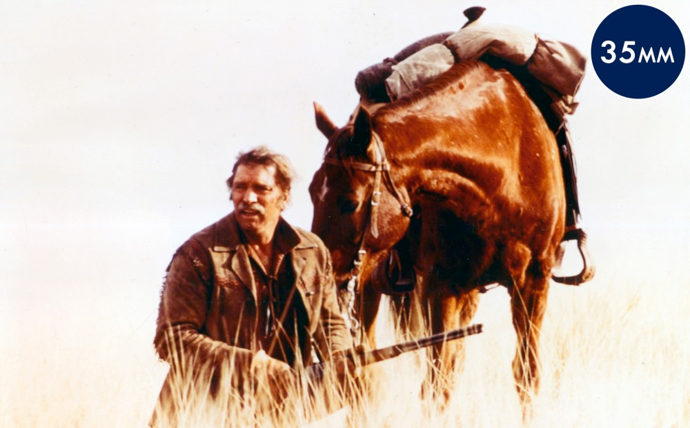 Actor Burt Lancaster holds a gun, standing in a field with his brown horse.
