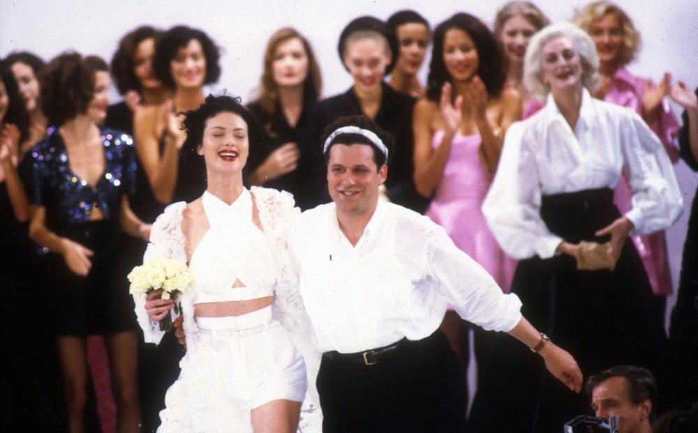 Fashion designer and subject of UNZIPPED, Isaac Mizrahi, walks on a runway, surrounded by models.