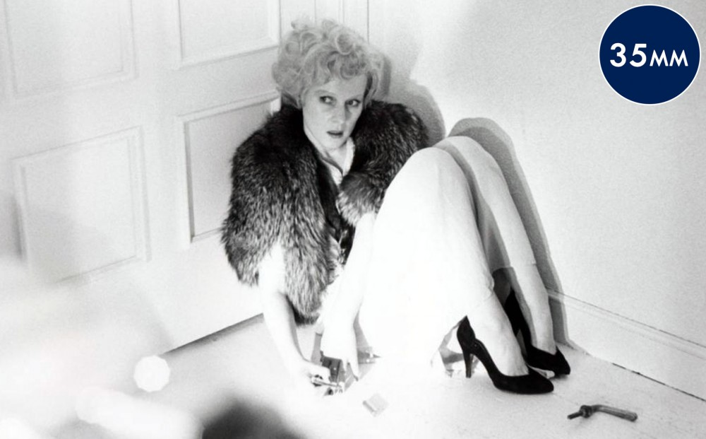 Actor Rosel Zech, wearing a fur stole and heels, sits on the ground, crouched against a doorway.