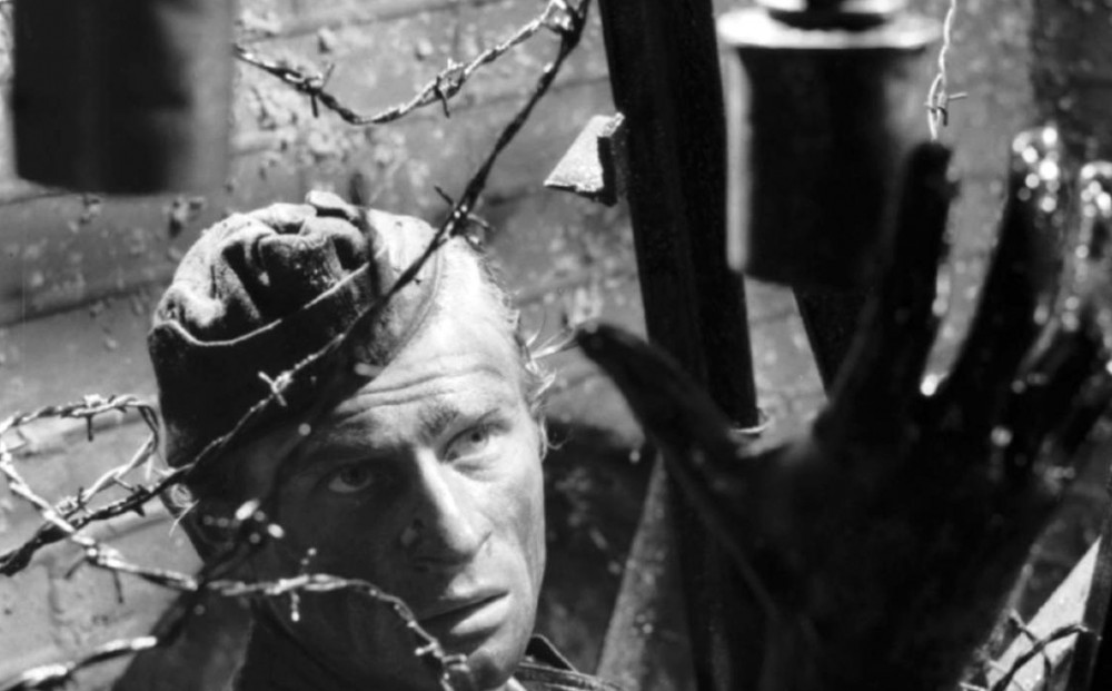 A man reaches through barbed wire.