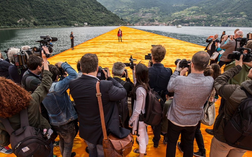 A crowd of photographers snap photographs of Christo, who stands at a distance, all on 'The Floating Piers.'